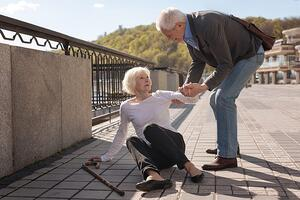 bigstock-Elderly-couple-lady-falling-186807634